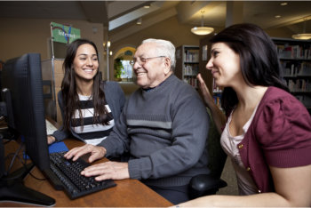 senior man using computer with two women