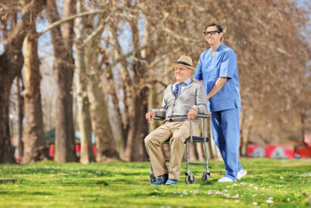 senior man in a wheel chair and male caregiver