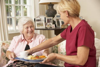 caregiver serving food to a senior woman